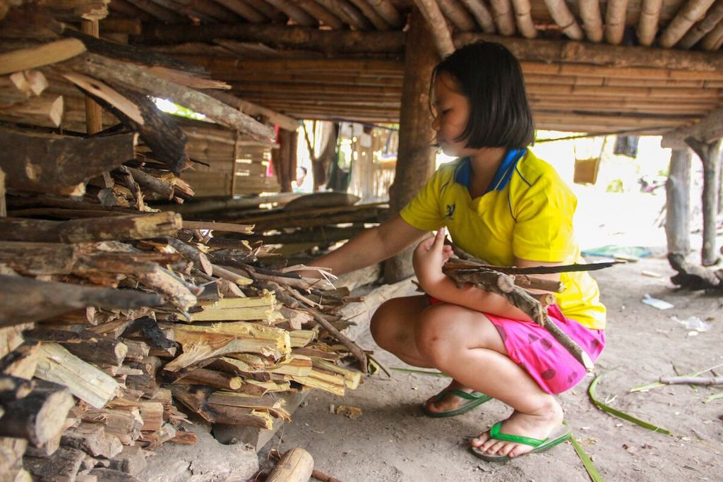 A Thai girl stacking wood.