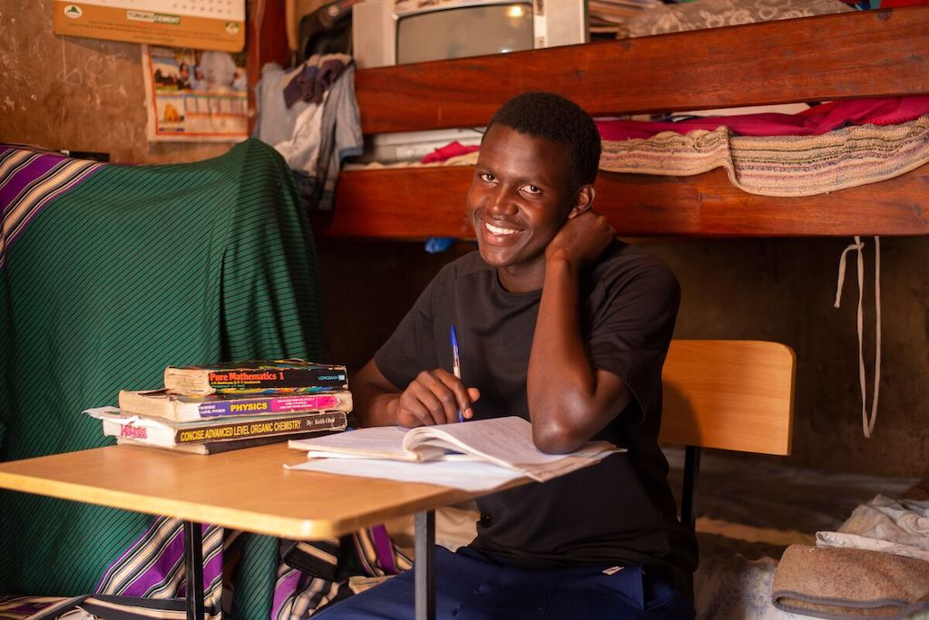A teen boy sits at a desk in his home doing homework.
