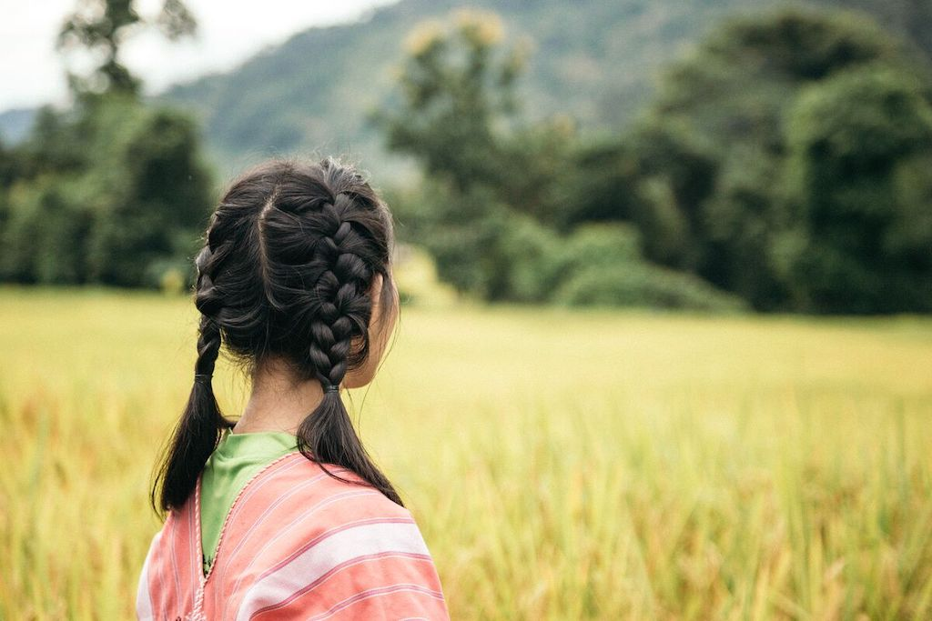 A silhouette of a Thai girl wearing a pink poncho and two braids.