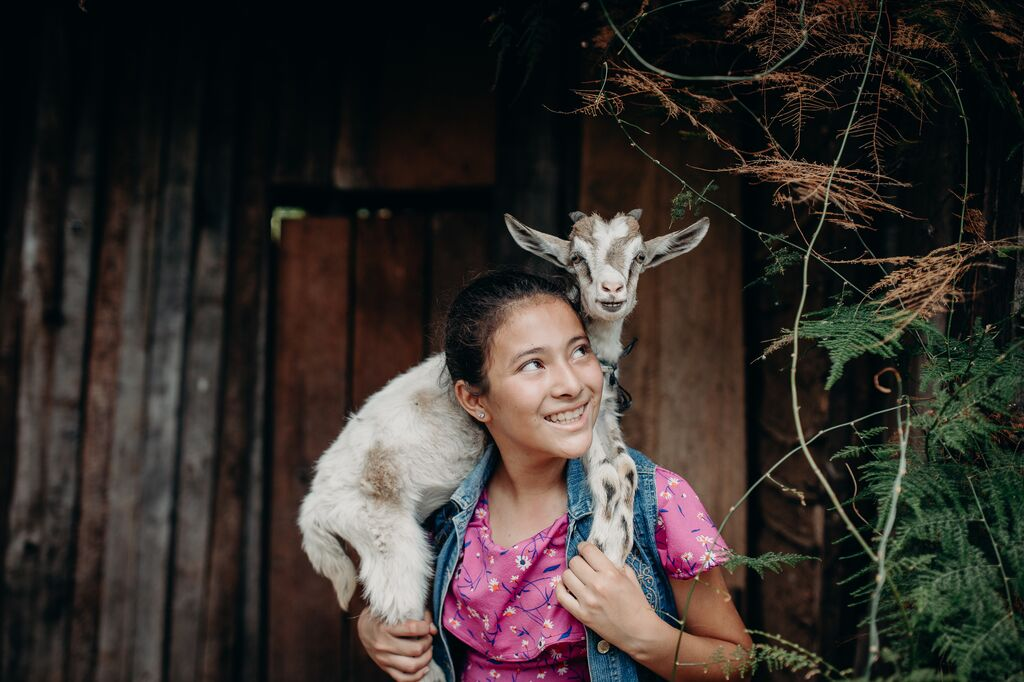 Girl wearing pink shirt carries a goat around her shoulders.