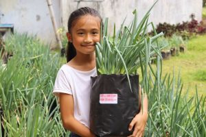 An Indonesian girl holds a large plant.