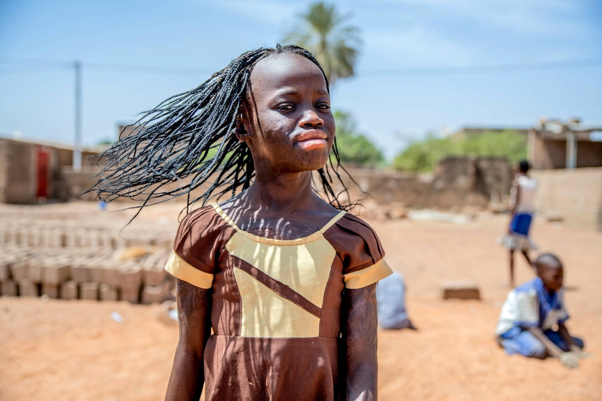 Girl wearing a brown dress turns her head and looks at the camera with confidence. Her hair is flowing in the wind.