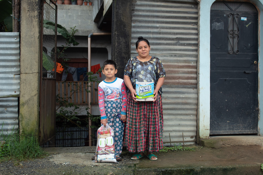 A mother and son stand together holding bags of supplies.