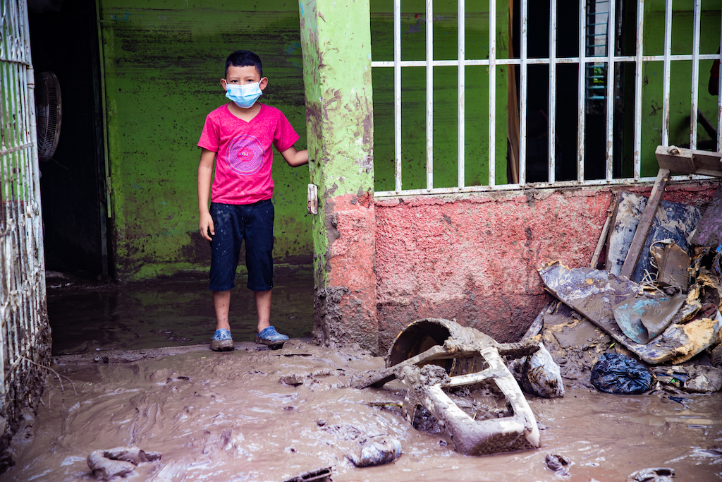 A boy in a face mask and a red shirt stands in the green doorway of his home. The floor and walls are muddy.