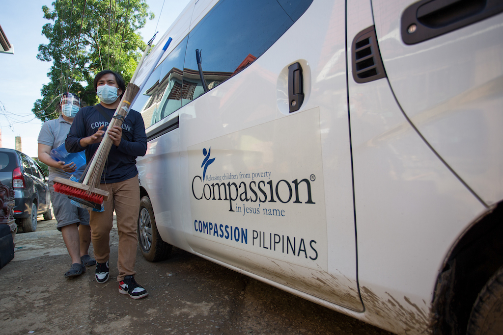 Two men in face masks beside a van with the Compassion logo on the side.