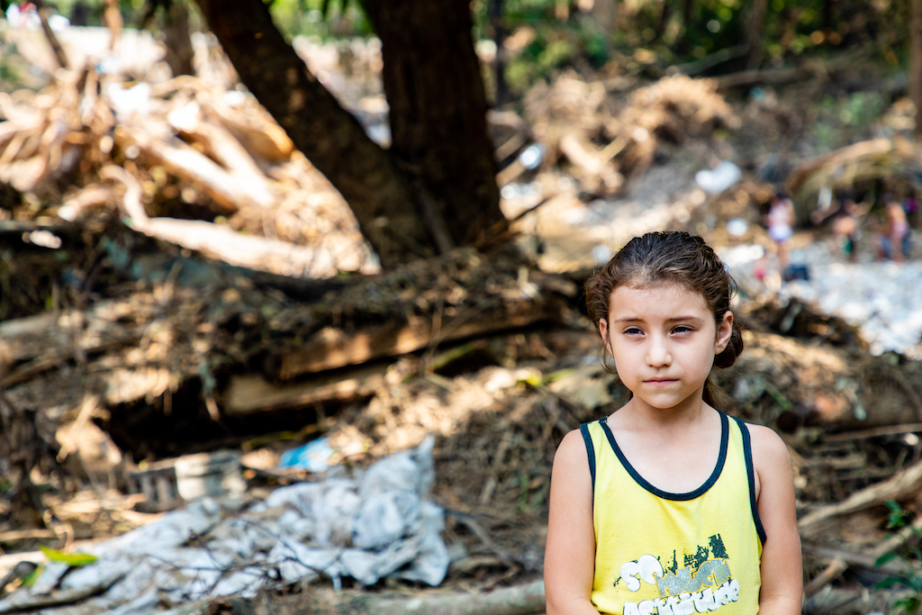 A young Honduran girl stands in the rubble of her home.
