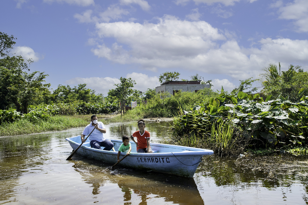 A man and two children ride a blue fishing boat through a flooded street.