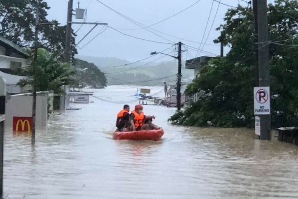 A small raft with several rescue team members on board floats through a flooded street.