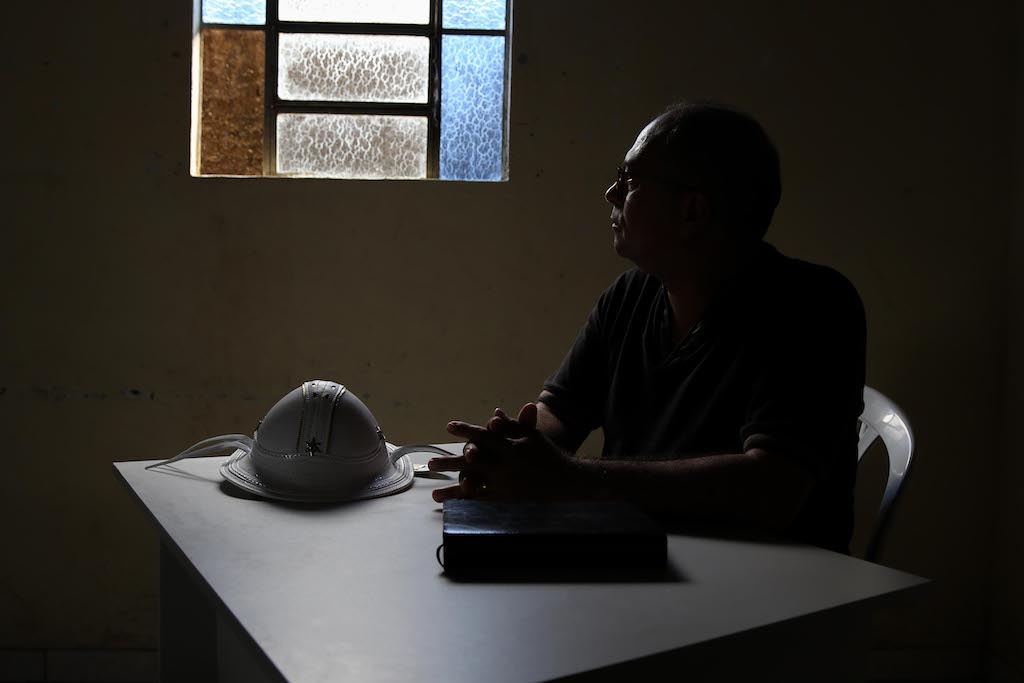 A silhouette of Pastor Linaldo, sitting at a table inside his church building.