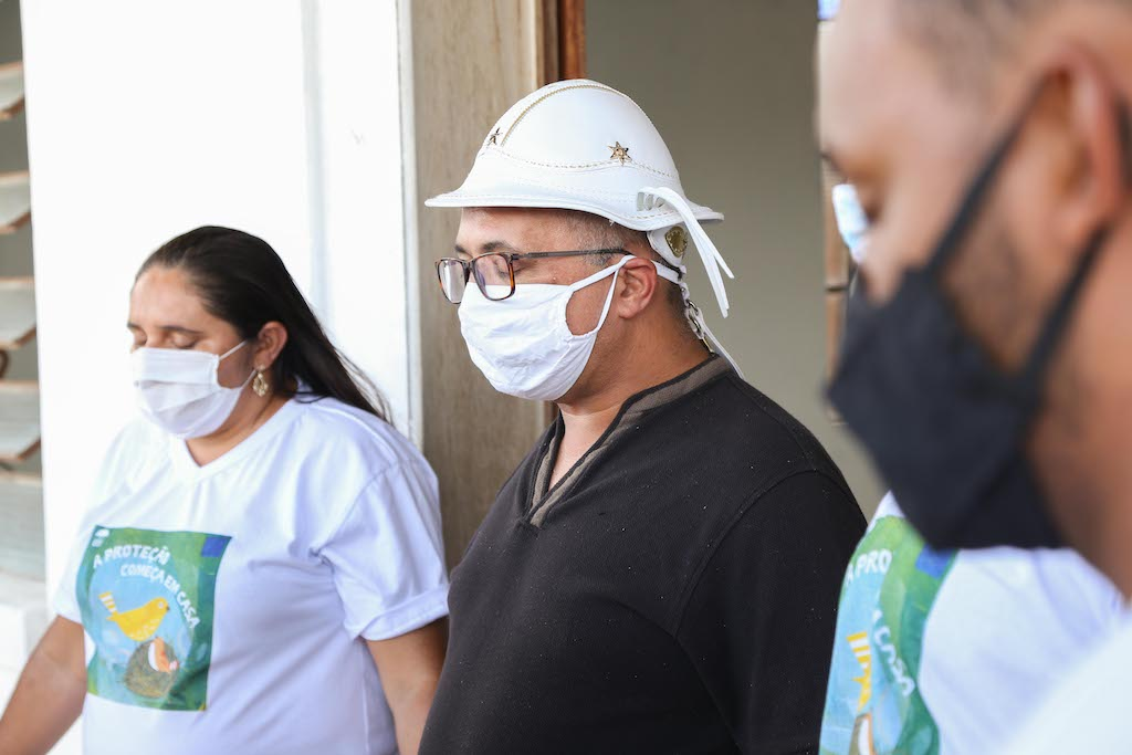 All wearing protective face masks, Pastor Linaldo and a group of volunteers pray together.