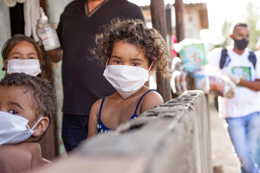 A young girl in a mask stands in front of her home, with Pastor Linaldo in the background holding a bottle of hand sanitizer.
