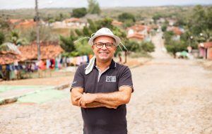 Pastor Linaldo stands in a roadway in his community, smiling with his arms crossed and wearing a dark polo shirt and a white hat.