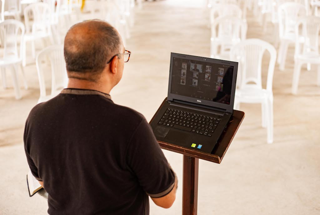Pastor Linaldo stands in front of a laptop with a Zoom meeting open.