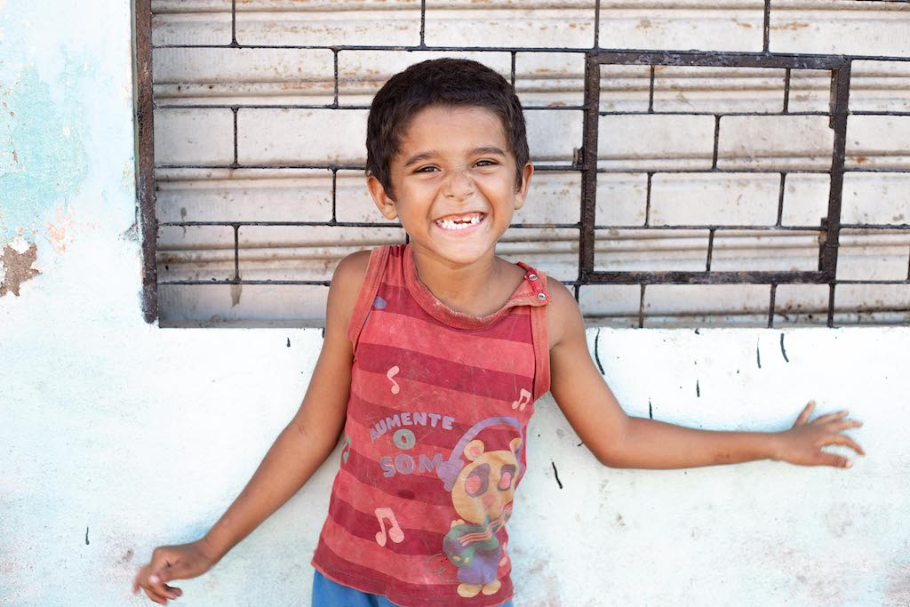 A child from Pastor Linaldo's community stands against a wall, smiling and wearing a red shirt.