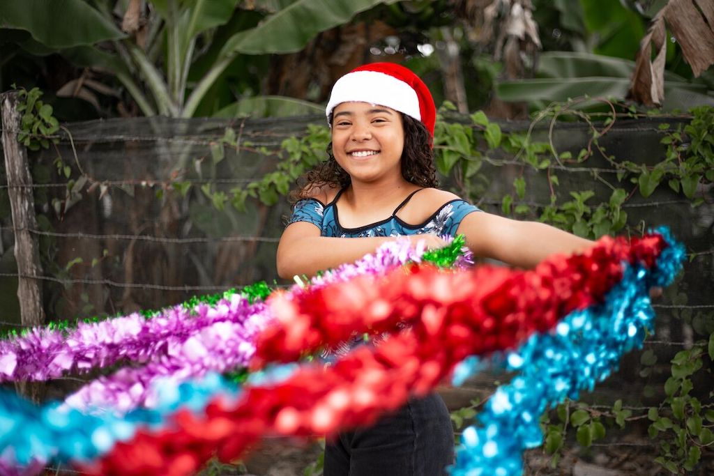 Young girl stands infront of trees wearing a santa hat and golding colourful tinsel.