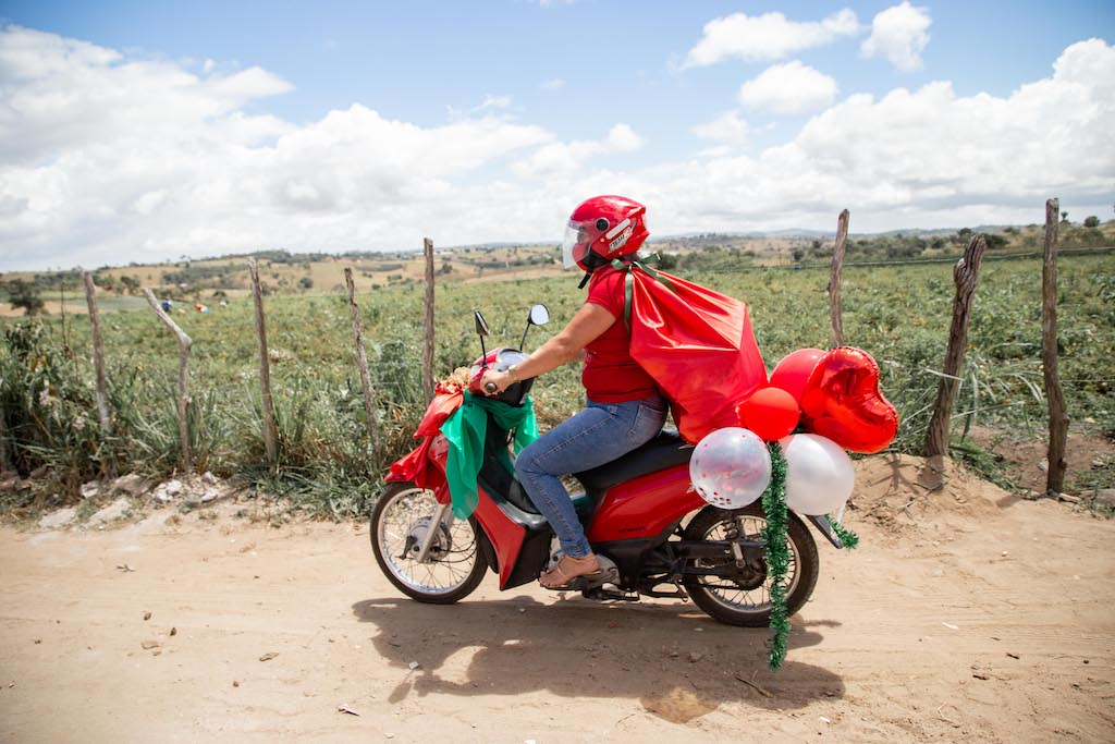 A volunteer is on a motorcycle wearing a red cape, a red helmet, with balloons and streamers flying off of it.
