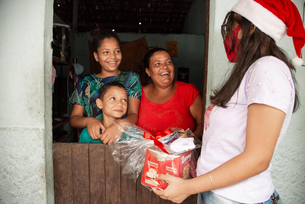 A volunteer wearing a Santa hat and a mask brings gifts to a family of 3 who is smiling behind their door.