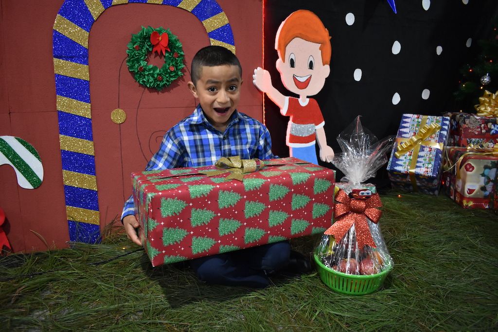 Little boy wearing a blue plaid shirt sits with a big gift on his lap, with a big happy surprised look on his face.