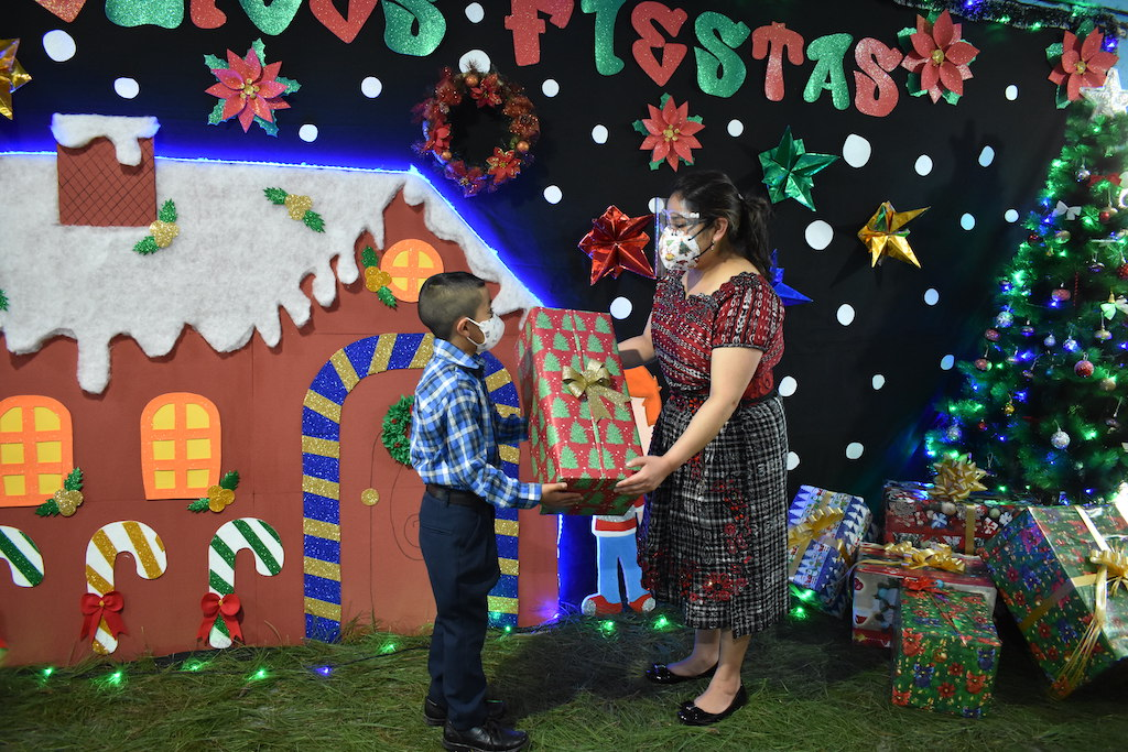 A woman wearing a mask passes a gift to a little boy wearing a mask. There is a painted gingerbread house in the background.