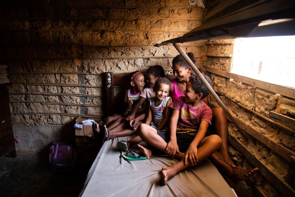 A family sits on a bed in their home.
