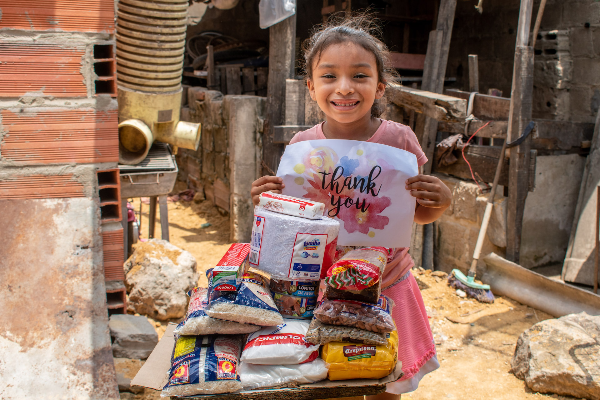 """In Colombia, a girl holds a sign that says """"Thank You"""", standing beside a grocery delivery from Compassion."""