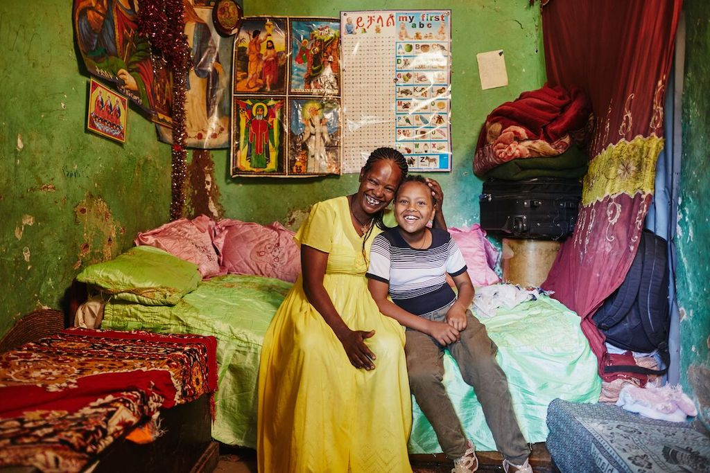 Tigist, in a yellow dress, is sitting on a bed with Yeabsera with their heads pressed together. The walls are green and there is a red curtain, blanket and table cloth.