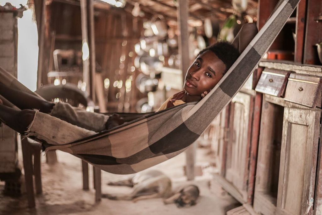 João lays in the hammock where he sleeps every night. The house where he and his family live has just one bedroom, so João and his brother sleep in the living room.