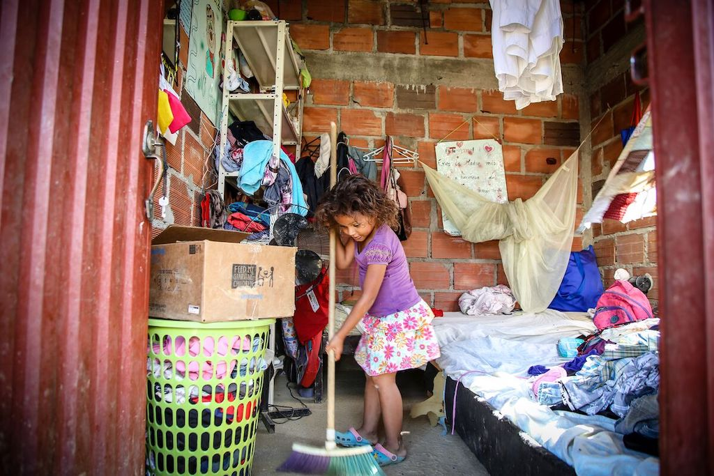 A girl in a purple shirt is standing inside her home holding a broom and sweeping. The walls are brick and she is next to two beds with clothes on them.