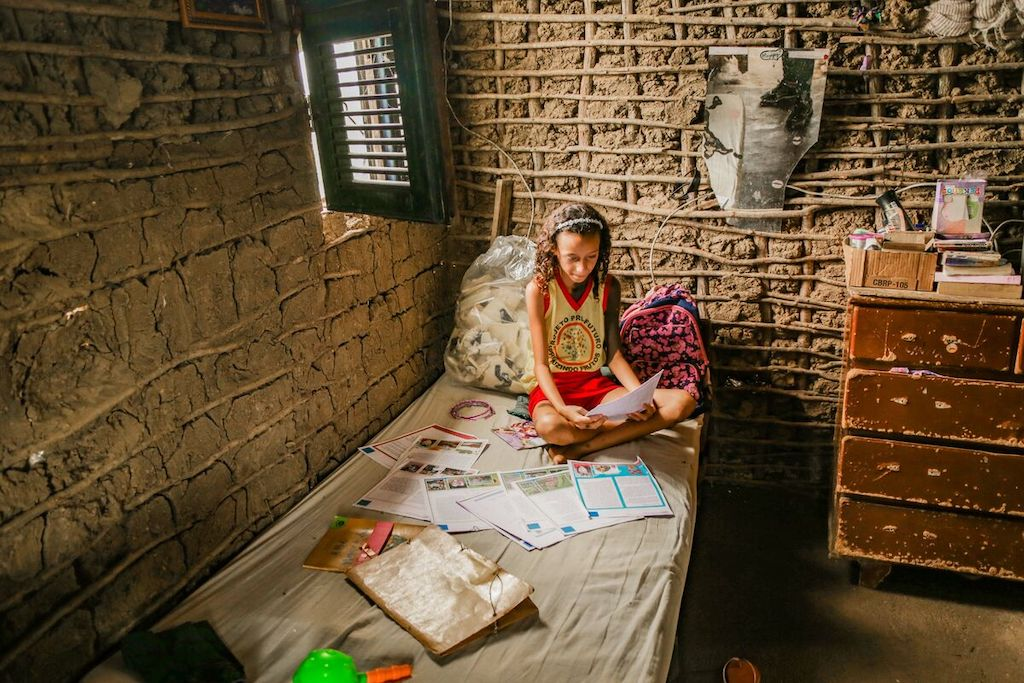 Kaylane reads one of her sponsor's letters on the bed she shares with her older sister every night. Kaylane is wearing a yellow shirt and red skirt.
