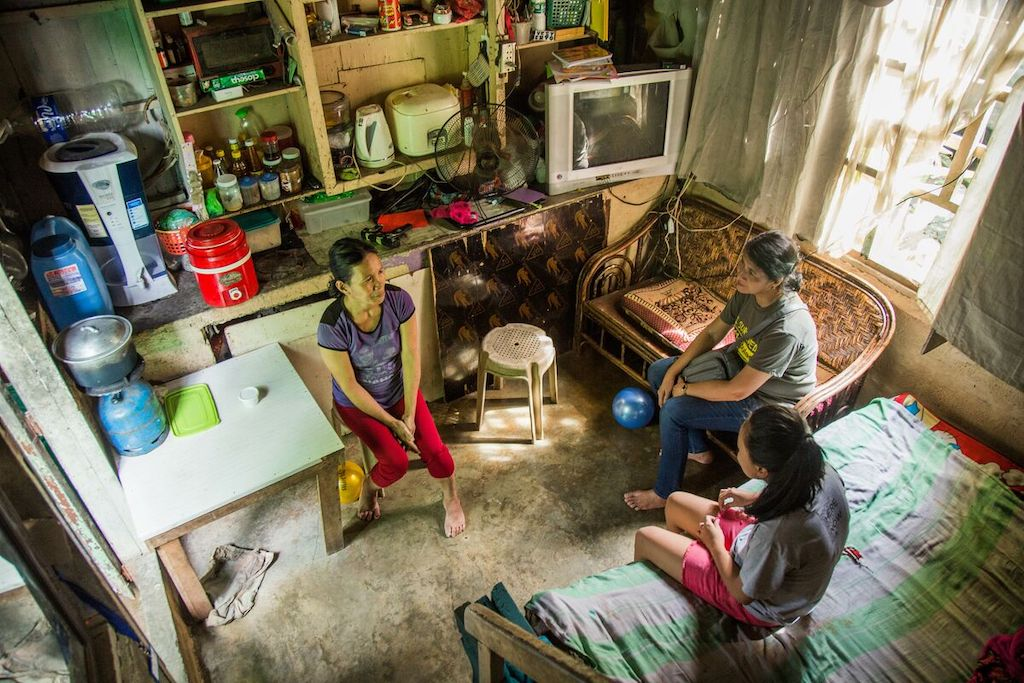 Jearvee with her mother Annalyn. They are being visited by Ruth Manzano, the project director of PH0206. They are sitting together in their small house.