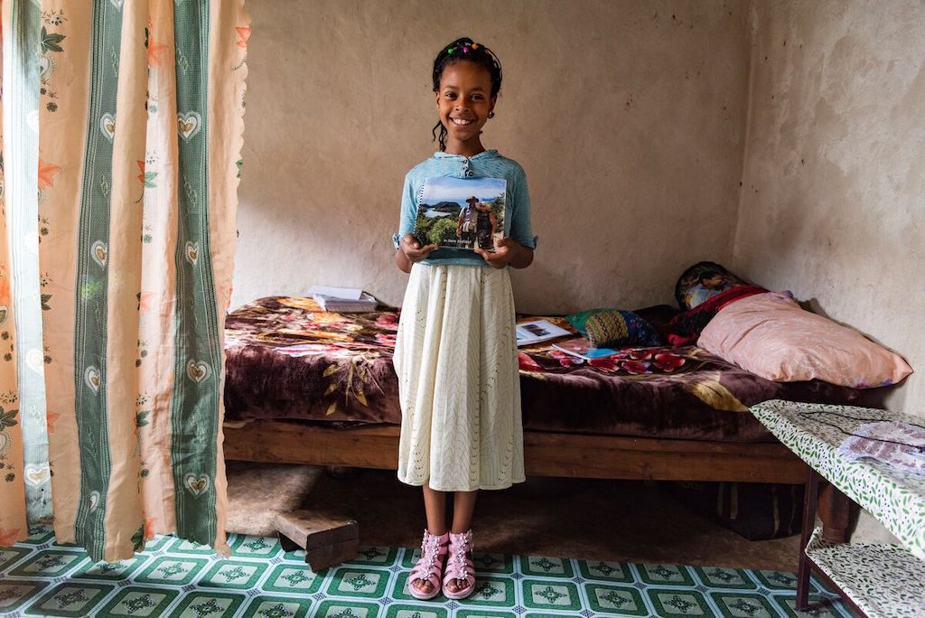 Kalkidan is wearing a blue shirt and white skirt. She is standing in her home in front of her bed, holding pictures of her sponsors.