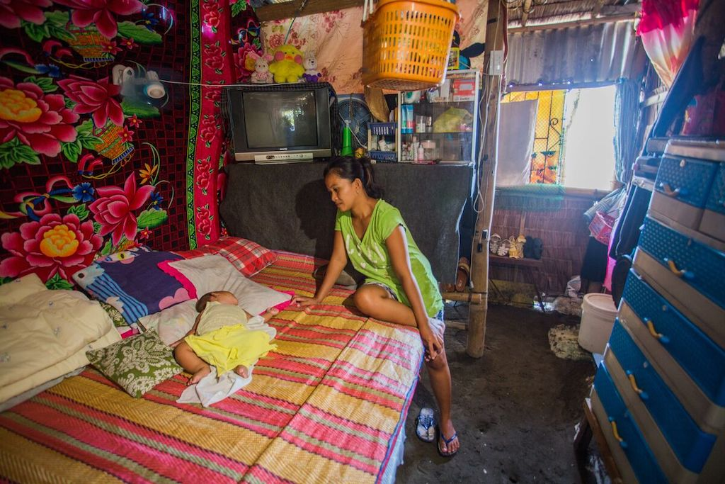 Jonalyn, wearing a green shirt, is sitting on a bed in her home looking at her baby, Ruela, who is sleeping. The house is very crowded.