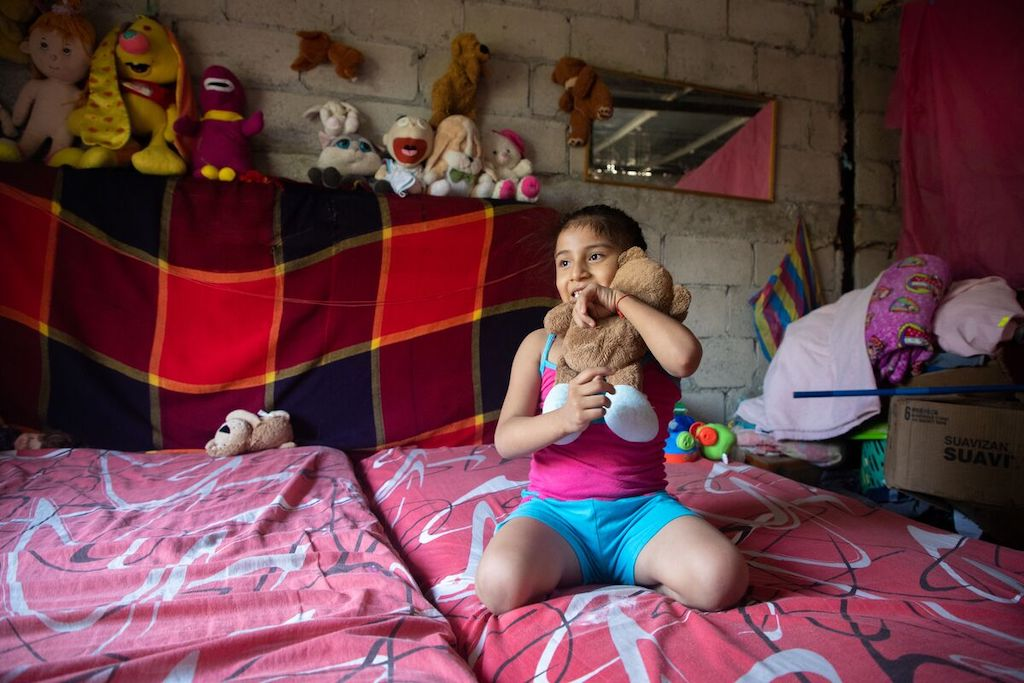 Maria Jose is wearing a pink shirt and blue shorts. She is sitting on her bed hugging her teddy bear. Behind her are her toys.