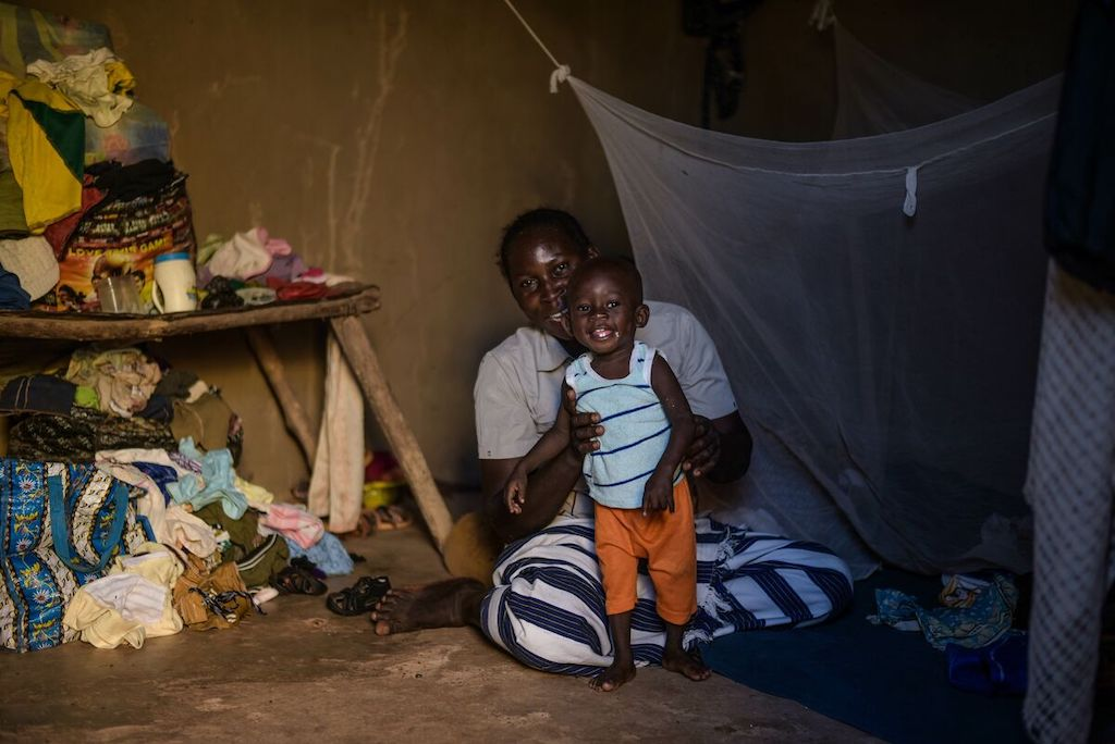 Yves and Bibata are siiting inside their home. On the left is a wooden table with clothes and other household belongings. Behind them is a mosquito net hanging from the wall.