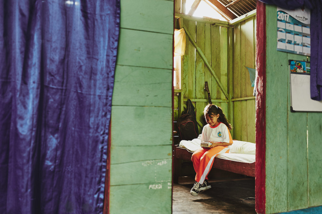 A girl in white and orange sits on a bed holding and looking at a book through a doorway with green wood walls, red trim and purple curtain.