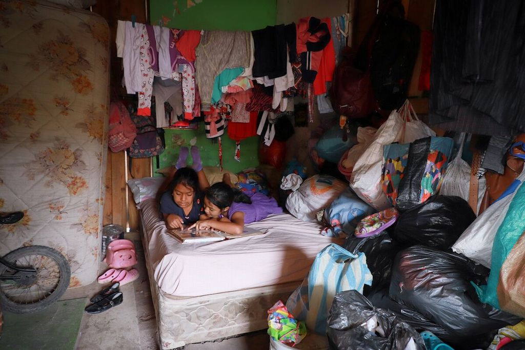 Yaretzi (left) and Julieth (right) read their sponsors' letters. They keep them in a photo album. Both of them are laying down on the bed they share with their Grandmother Yaretzi is wearing a gray dress with pink hearts on it and purple socks. Julieth is wearing a purple dress.