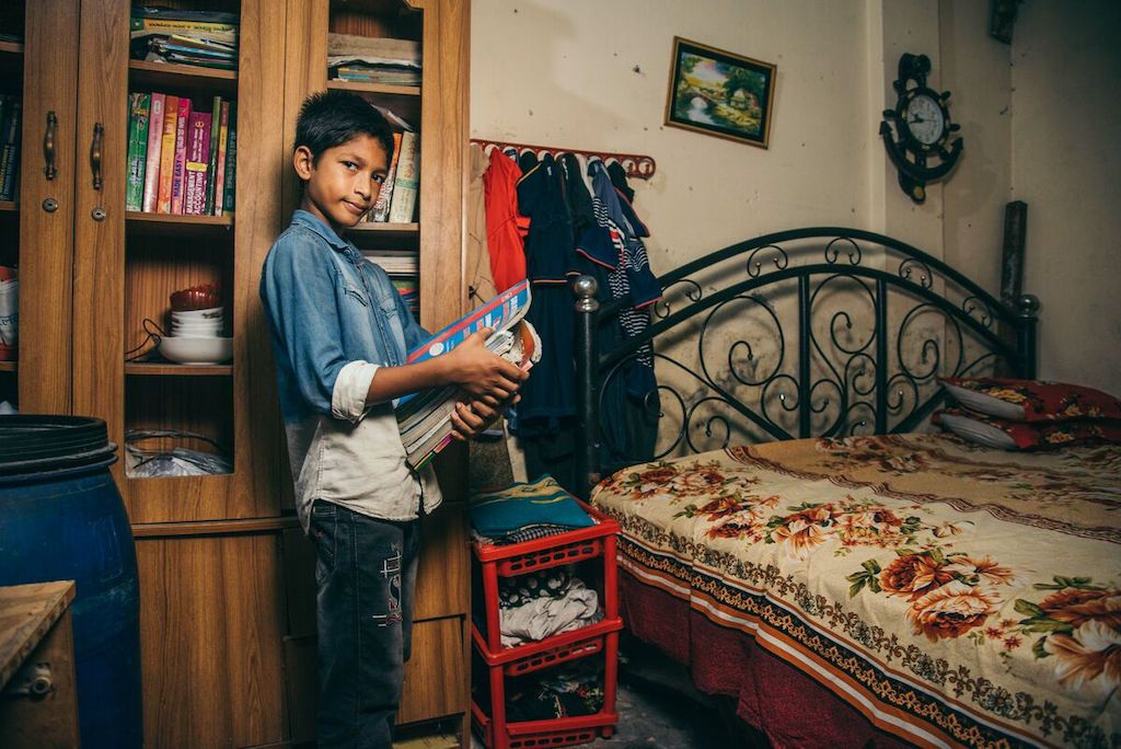 Shakib is wearing a denim shirt and jeans. He is standing in his room and behind him is a large cabinet full of his older siblings' books. He is holding an armful of books and next to him is his bed.