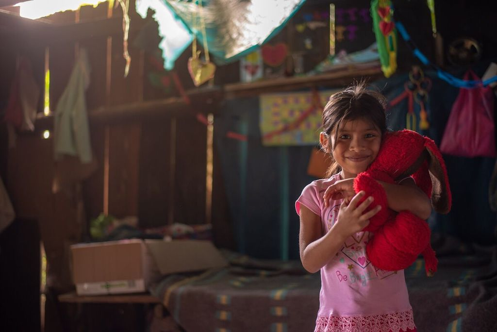 Elizabeth is holding her teddy bear in her room. Elizabeth is wearing a pink tee shirt and is smiling at the camera. There is a wooden fence behind her.