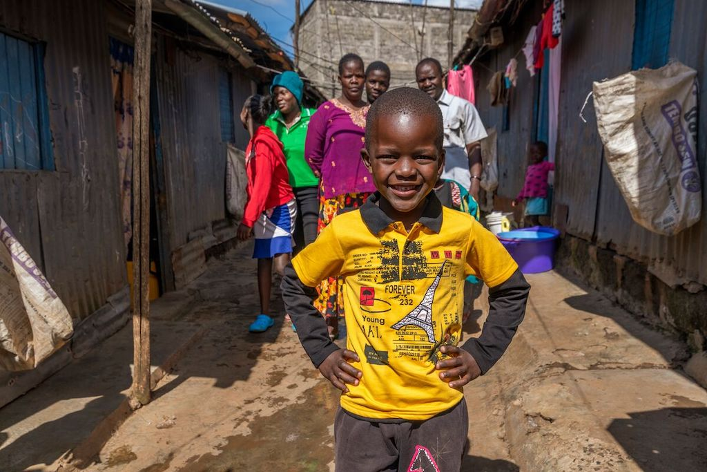 In Kenya, a boy in a yellow shirt stands with his hands on his hips, with his family standing behind him.