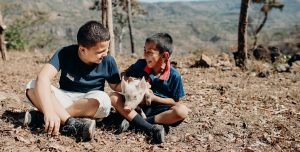 Two boy sit on the ground outside. One holds a young piglet and laughs.