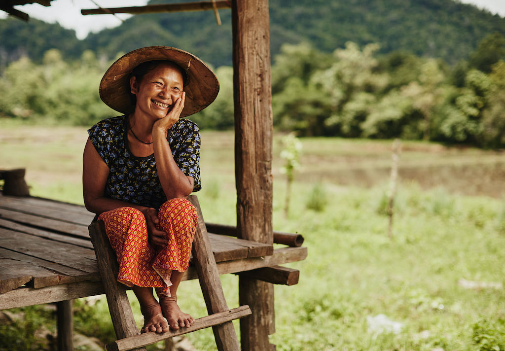 A Thai woman sits on the wooden steps of her home.