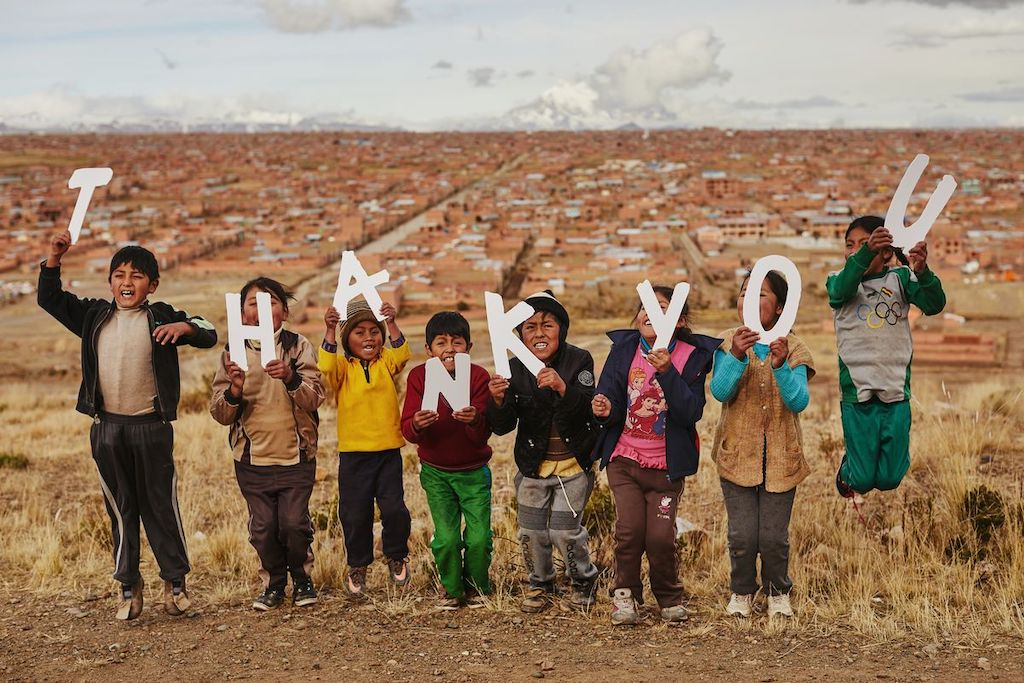 Children holding cutout letters that say 'thank you'.