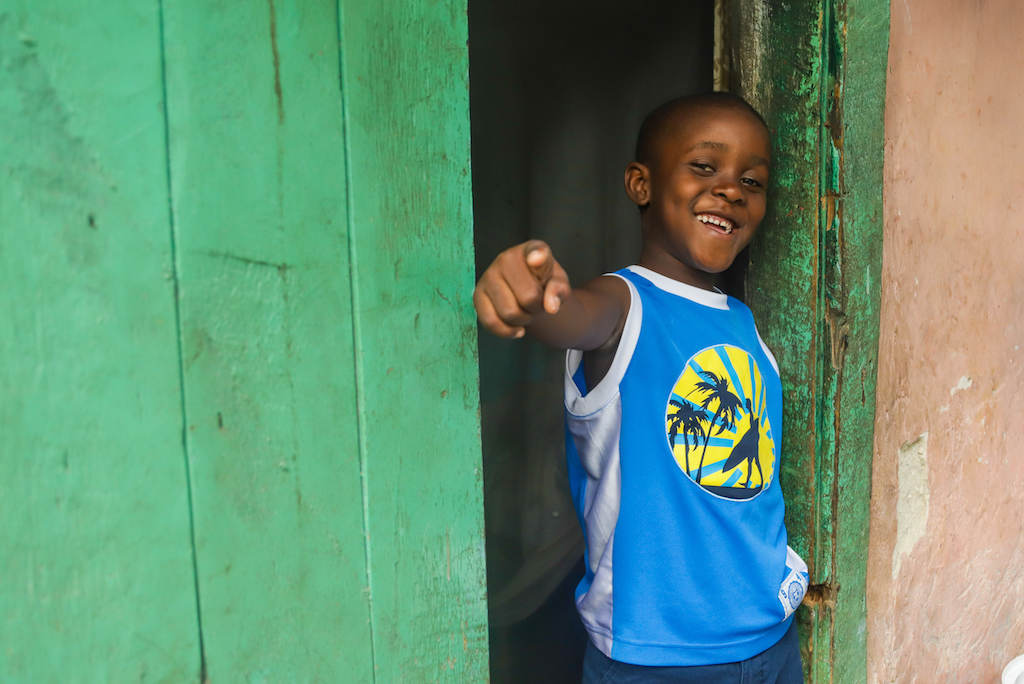 A boy in a blue tshirt stands in a green doorway smiling and pointing a finger in a pose.