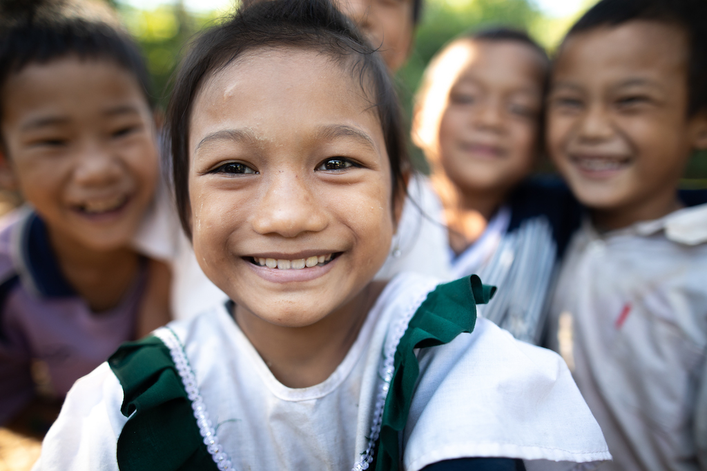A Thai girl wearing a white and green shirt, with other children in the background.