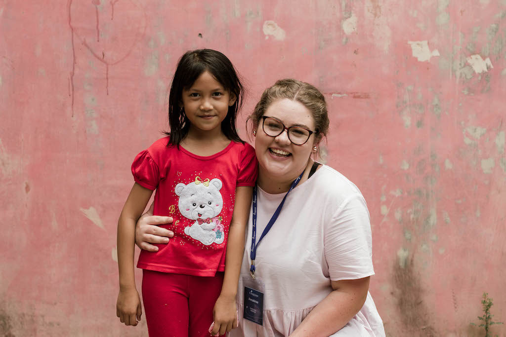 An young Australian woman has her arm around a young Indonesian girl, who is wearing red.