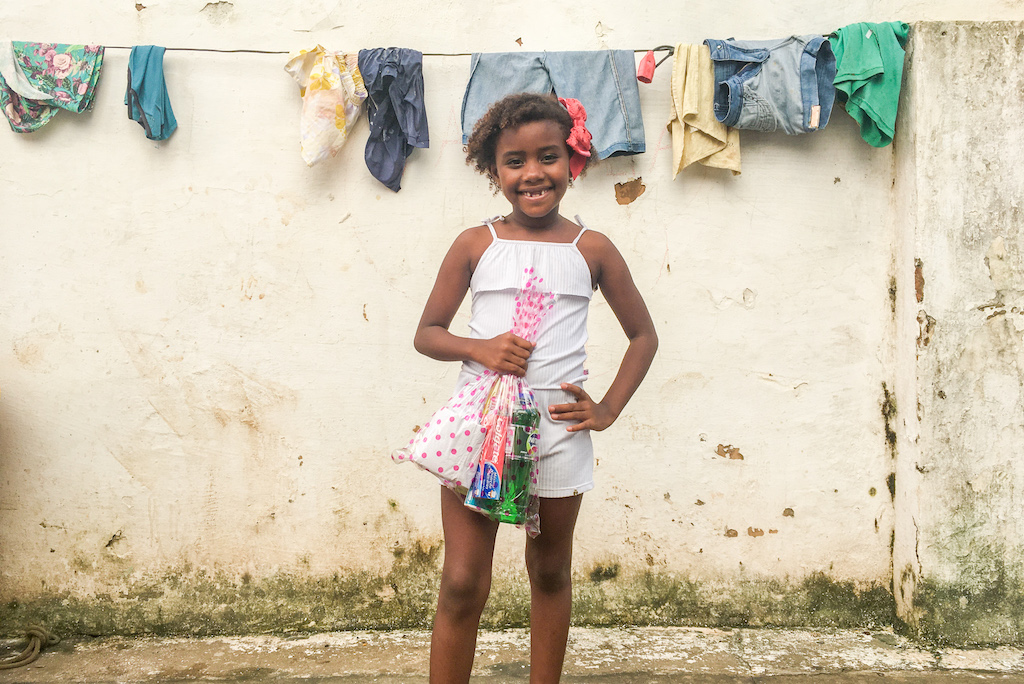 A girl in a white dress holds a hygiene kit.