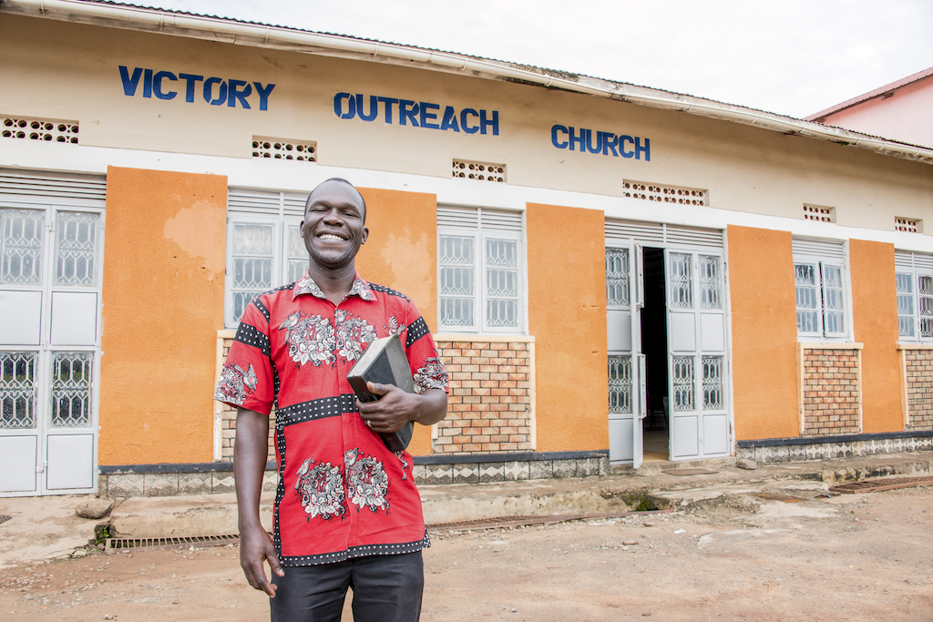 """A man stands holding a Bible in front of a building that says """"Victory Outreach Church""""."""