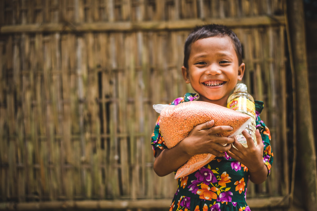 A young Bangladeshi child carrying an armful of groceries delivered by Compassion staff.