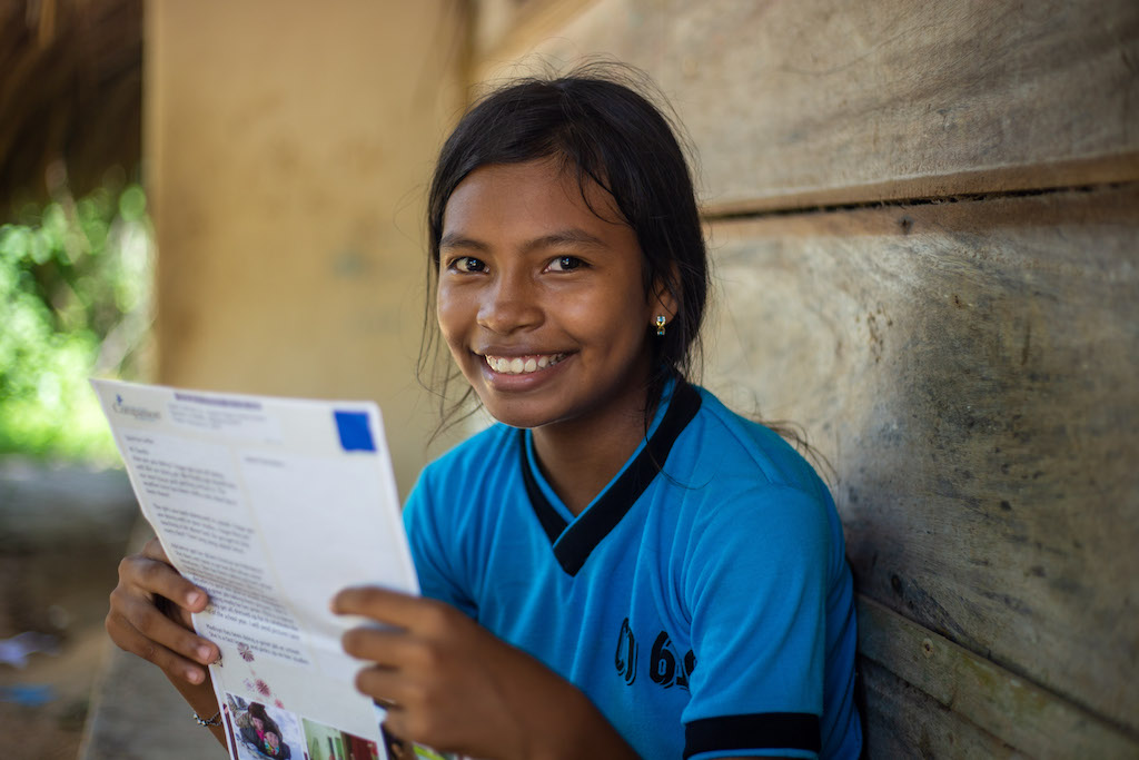 A Colombian girl in a blue t-shirt smiles as she reads a letter from her sponsor.