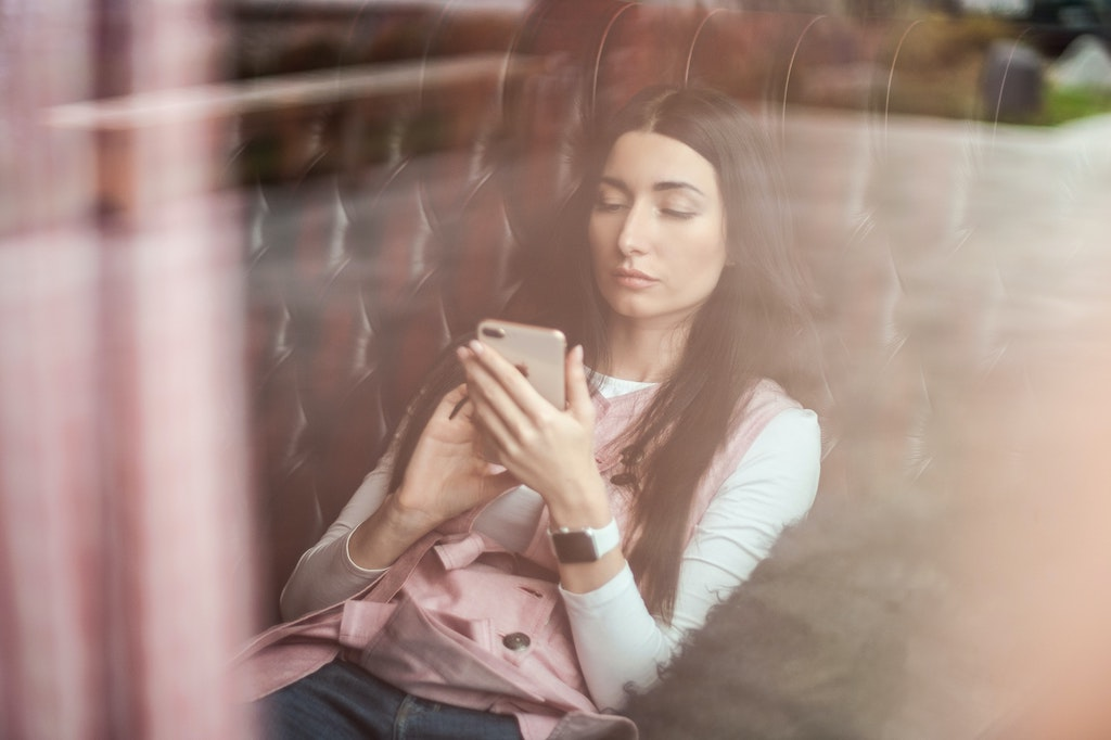 A woman leaning back in a chair and scrolling on her smart phone.